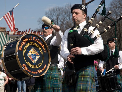 Bagpiper and Drummer representing the Knights of Columbus marching in St. Patrick's Day Parade, Park Slope, Brooklyn, New York. The Irish community is one of New York's major and important ethnic groups, and has been a significant proportion of the city's population since the waves of immigration in the late 1800s and New York City today has the largest number of Irish-Americans of any city in America.  Parades are an important part of Irish culture.. : Stock Photo
