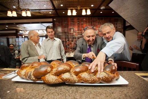 (L-R) Ernest Wachtel, grandfather, Josh Lebewohl, Fyvush Finkel, and Jack Lebewohl. The famed Yiddish theater and television star Fyvush Finkel performs a blessing and cuts a loaf of challah at the opening of the 2nd Avenue Deli branch on the Upper East Side of New York on Tuesday, August 16, 2011. : Stock Photo