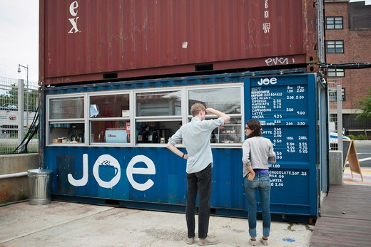 Customers peruse the menu at Joe, a coffee bar, in the Dekalb Market in downtown Brooklyn in New York, seen on Saturday, September 10, 2011.  The market, which uses decorated and modified shipping containers as kiosks for its vendors, is located in the high density area of downtown Brooklyn and includes vendors selling food, clothing and accessories, all from local sellers. : Stock Photo