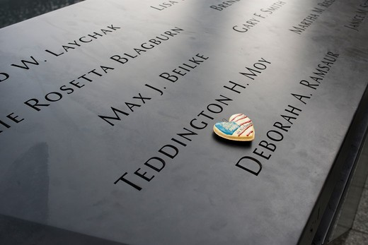 Visitors leave remembrances on names in the National 9/11 Memorial Plaza in the World Trade Center site in New York Wednesday, September 14, 2011. The memorial consists of twin memorial pools on the footprints of the World Trade Center and a plaza planted with more than 400 swamp white oak trees. : Stock Photo