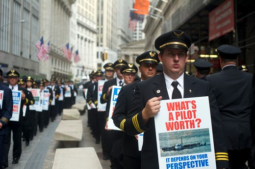 United and Continental pilots conduct an informational picket outside the New York Stock Exchange on Tuesday, September 27, 2011 on the eve of the one-year anniversary of the corporate merger. The pilots, represented by ALPA, are protesting the pace of their collective bargaining negotiations.  (© Frances M. Roberts) : Stock Photo