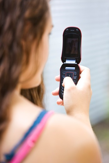 Teenage girl text messaging on a mobile phone : Stock Photo
