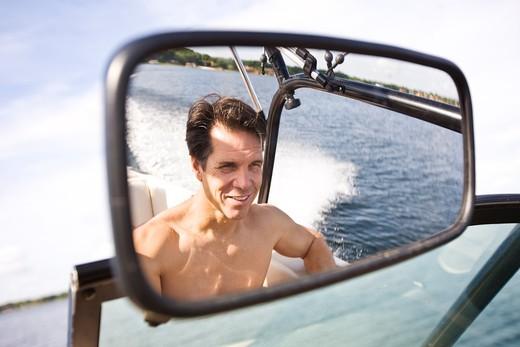 Stock Photo: 4061-131 Reflection of a mature man in rear-view mirror of a motorboat