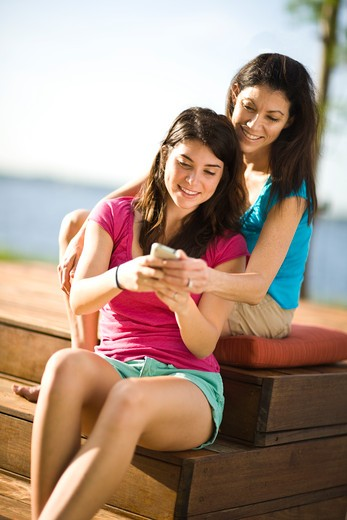 Young woman text messaging on a mobile phone with her mother behind her : Stock Photo