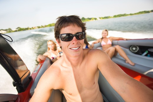Young man with his friends in a motorboat : Stock Photo