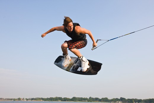 Young man performing wakeboarding stunts : Stock Photo