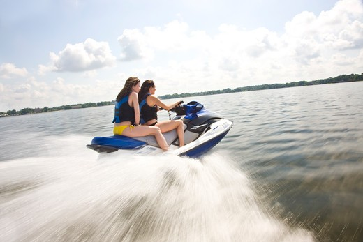 Two young women riding a jet ski : Stock Photo