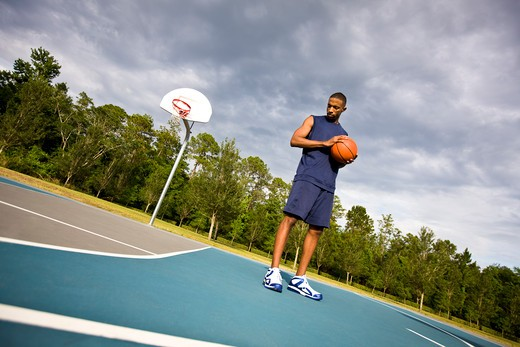Young man holding basketball on outdoor court : Stock Photo