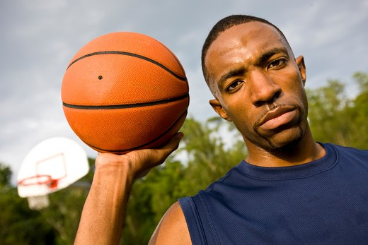Portrait of a young man holding a basketball : Stock Photo
