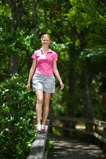 Stock Photo: 4061R-230 Mid adult woman walking on a railing