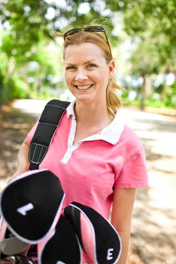 Mid adult woman carrying a golf bag : Stock Photo
