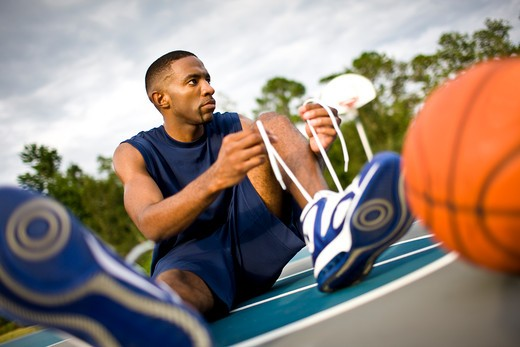 Stock Photo: 4061R-242C Young man tying his shoelaces
