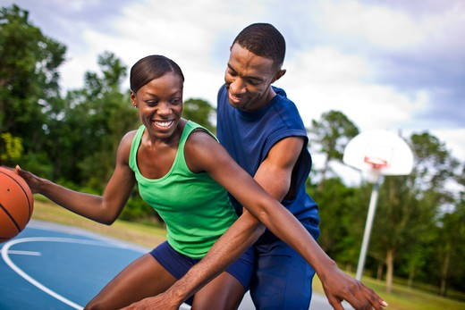 Young couple playing basketball : Stock Photo
