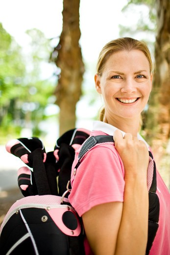 Stock Photo: 4061R-251B Mid adult woman carrying a golf bag