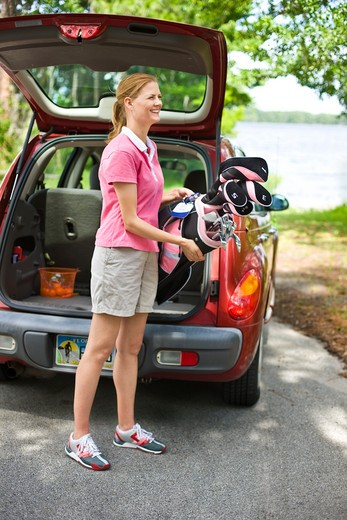 Stock Photo: 4061R-252A Mid adult woman putting a golf bag into a car trunk