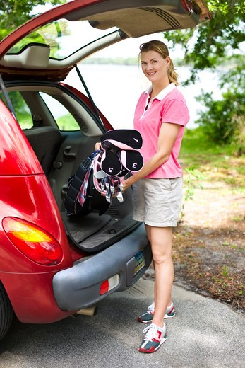 Mid adult woman putting a golf bag into a car trunk : Stock Photo