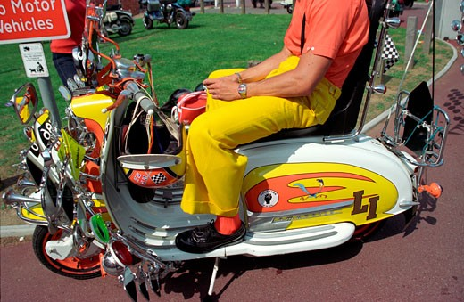 Stock Photo: 4062-1314 Mod Will Vincent wearing matching shirt and trousers on his orange and yellow 'Roadrunner' Lambretta LI scooter Isle of Wight August 2000.