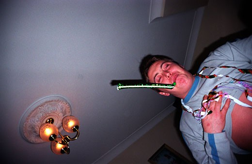Man with silly string around his neck blowing a party whistle : Stock Photo