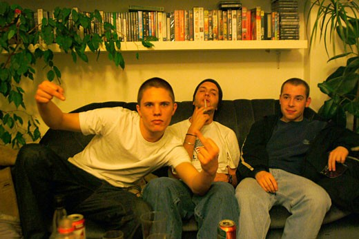 Group of friends chilling on the sofa; smoking a spliff; one giving the finger; UK; 2000's : Stock Photo