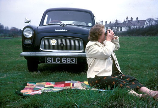 Stock Photo: 4062-1644 Woman admiring the view; sitting next to her Ford Perfect; UK; 1963
