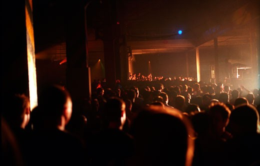 Silhouetted crowd watching the stage at Tribal Gathering Warehouse Party; Manchester; UK; August 2003 : Stock Photo