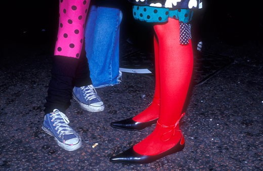 Stock Photo: 4062-1768 Converse sneakers; leg warmers; spotted tights; red tights: close up detail of clubbers' footwear and legwear outside Electro club NagNagNag @ Ghetto; London; 2003.