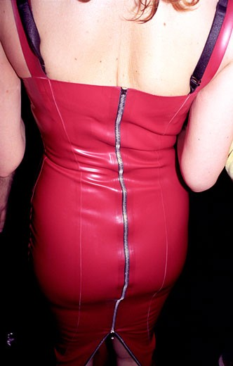 Woman in red pvc skirt with zip riding up the back; UK 2000s : Stock Photo