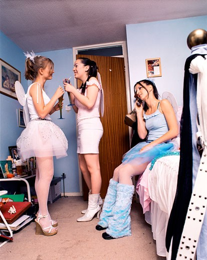 Three teenage girl clubbers; dressed in fairy costumes; one on the phone; in their room; UK 2002 : Stock Photo