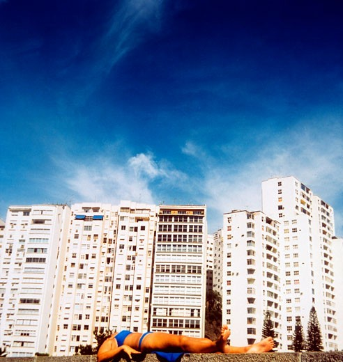 A woman lying on a wall sunbathing in front of giant apartment blocks; 2000's : Stock Photo