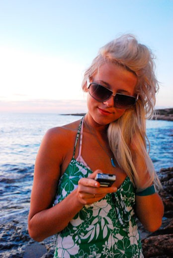 Stock Photo: 4062-2623 A portrait of a sexy young girl; texting with a mobile phone; on the beach at sunset; Ibiza; 2006