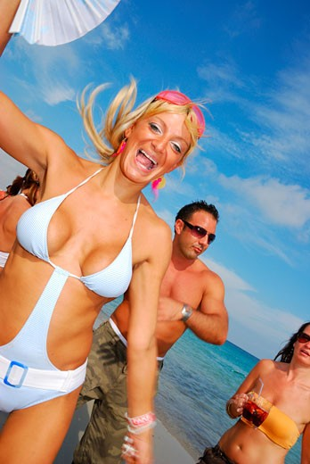 A woman with a group of friends dancing on the beach at Bora Bora; Playa D'en Bossa; Ibiza; 2006 : Stock Photo