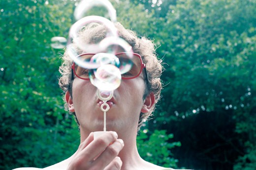 Boy on a hot summer day blowing soap-bubbles;UK 2006 : Stock Photo