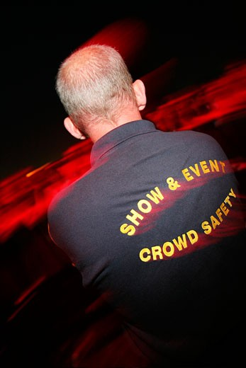 A crowd security guard, from behind, Isle of Wight Festival, June 2007 : Stock Photo