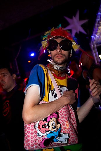 A guy wearing a colourful feather hat and Tshirt with big sunglasses, holding a bag, Space opening party, Ibiza 2007 : Stock Photo