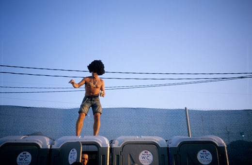 A man in an afro wig dancing on top of portable toilets. FIB 07. International Festival of Benicassim. Spain 2007 : Stock Photo