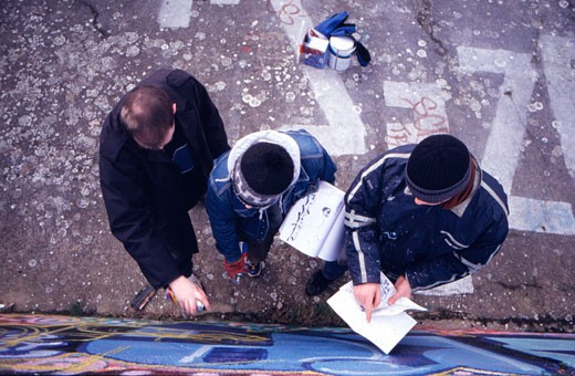 Graffiti artists spraying a mural on a wall, UK, 2000's : Stock Photo