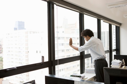 Businessman looking out from a window : Stock Photo