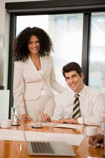 Businessman signing documents with his secretary standing beside him : Stock Photo