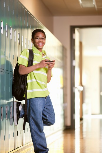 Stock Photo: 4064-176 Middle school student text messaging on a mobile phone