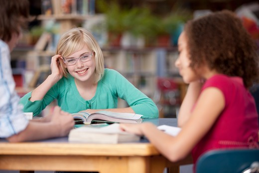 Middle school students talking in a library : Stock Photo