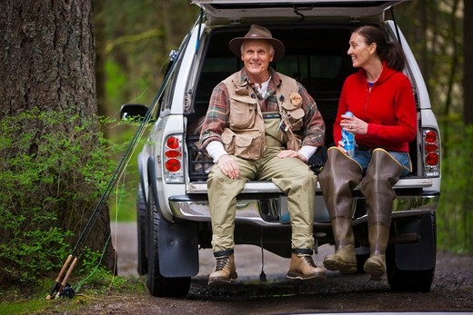 Stock Photo: 4064R-219 USA, Washington, Vancouver, Smiling couple sitting in back of car after fishing