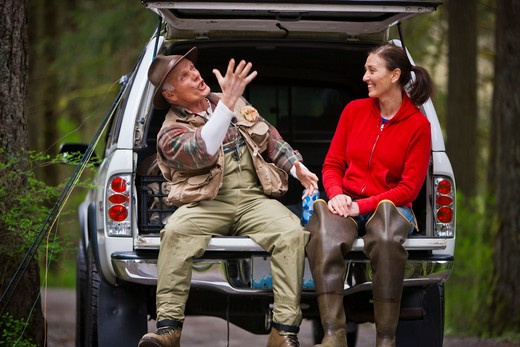 Stock Photo: 4064R-222 USA, Washington, Vancouver, Smiling couple sitting in back of car after fishing