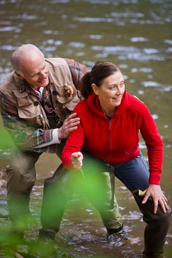 USA, Washington, Vancouver, Couple skipping stones on river : Stock Photo