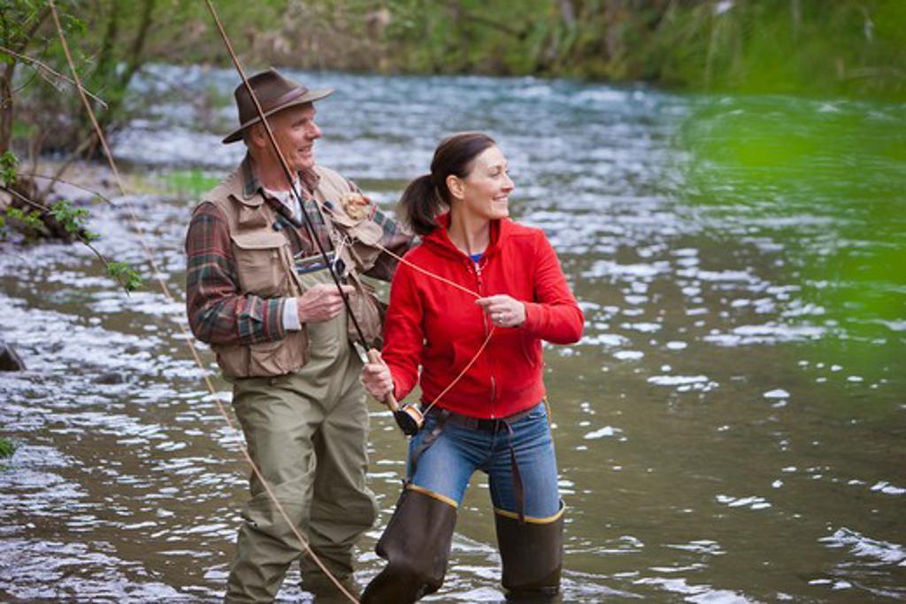 Stock Photo: 4064R-259 USA, Washington, Vancouver, Smiling couple fishing in river