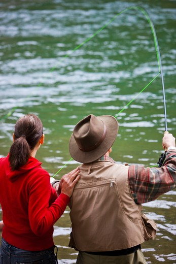 Stock Photo: 4064R-263 USA, Washington, Vancouver, Rear view of couple fishing in river