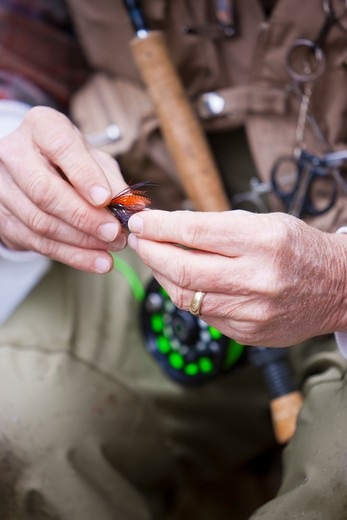 Stock Photo: 4064R-278 USA, Washington, Vancouver, Close-up of fisherman's hands tying fly onto line