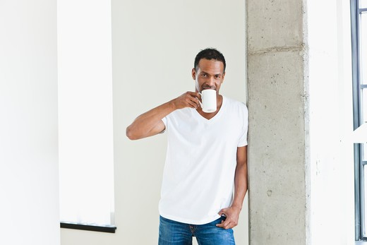 Man standing with coffee cup in loft apartment : Stock Photo