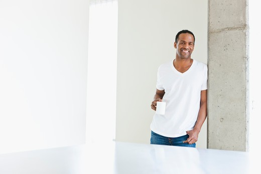 Stock Photo: 4064R-344 Man standing with coffee cup in loft apartment