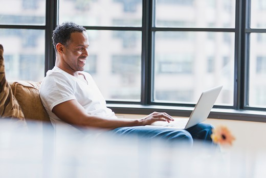 Man using laptop in loft apartment : Stock Photo