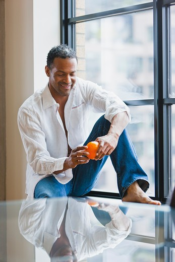 Stock Photo: 4064R-354 Man relaxing on window sill in loft apartment